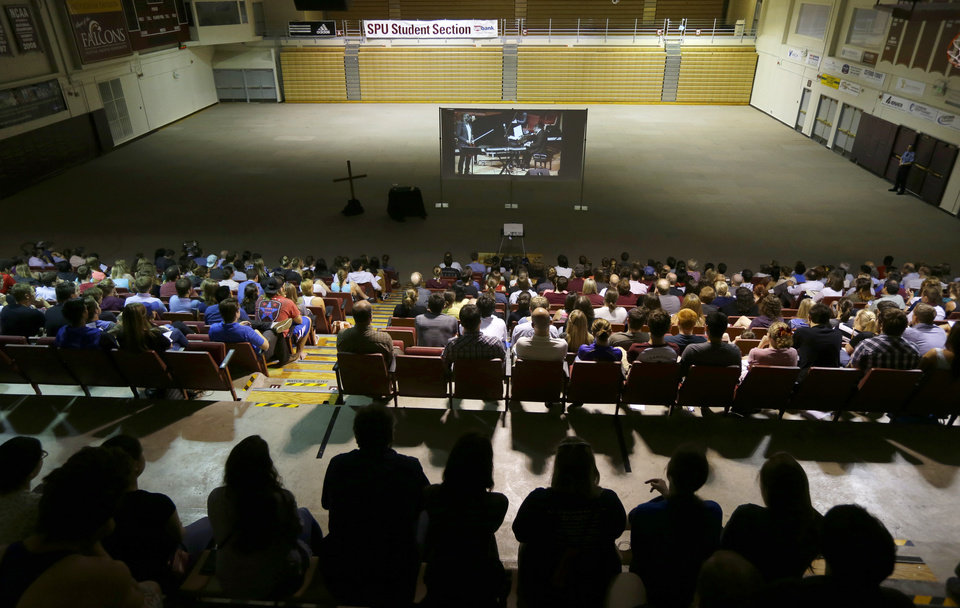 Photo - Students and other attendees sit in Royal Brougham Pavilion, an overflow site for a broadcast of a prayer service, at Seattle Pacific University, on Friday, June 6, 2014 in Seattle. The service was held a day after a fatal shooting at the school. (AP Photo/Ted S. Warren)