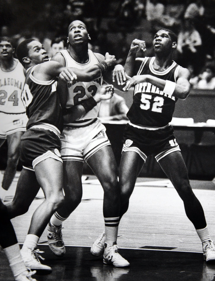 Photo - Former OU basketball player Wayman Tisdale. Despite the strong-arm tactics of Northwestern's Troy Turner (50) and George Jones, OU's Wayman Tisdale still broke the Big Eight career scoring mark on Saturday. Staff photo by Doug Hoke. Photo taken unknown, photo published 1/13/1985 in The Daily Oklahoman. ORG XMIT: KOD