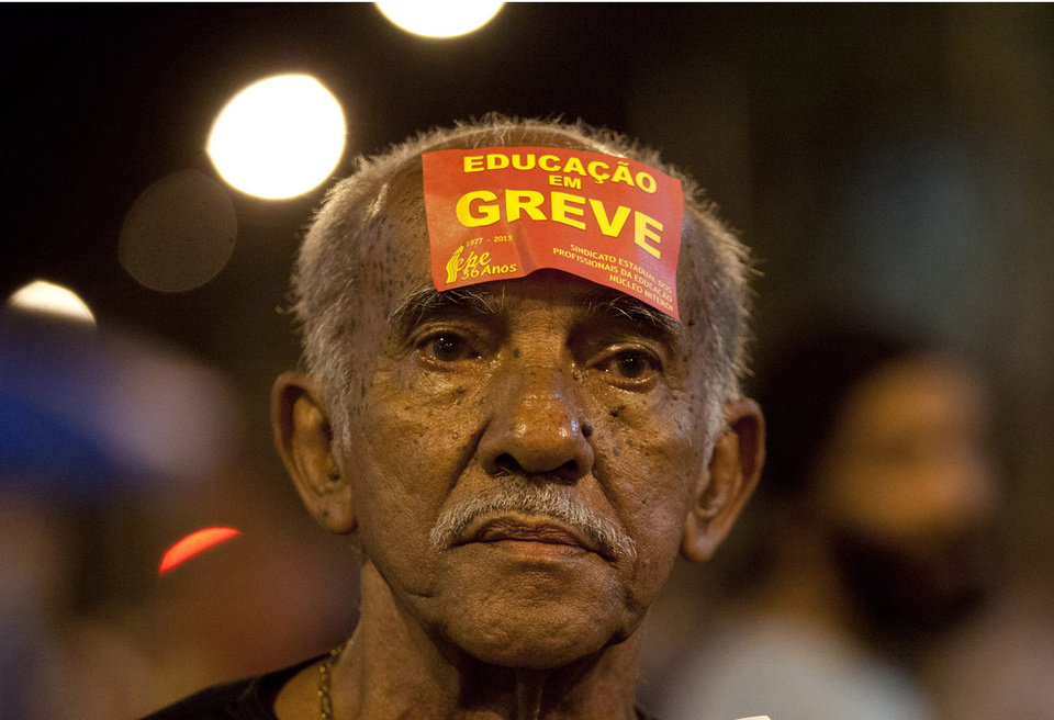 Photo - An education worker wears a sticker on his head that reads in Portuguese;