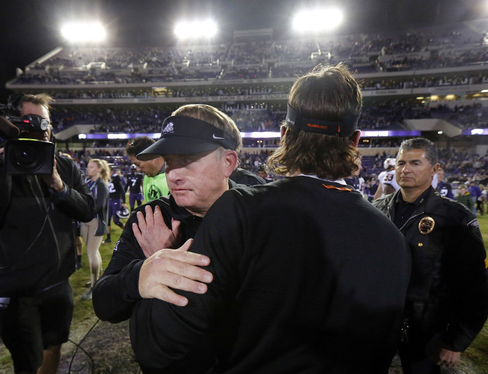 Photo - TCU coach Gary Patterson, front left, is congratulated on the TCU win by Oklahoma State coach Mike Gundy following an NCAA college football game in Fort Worth, Texas, Saturday, Nov. 24, 2018. TCU won 31-24. (Tom Fox/The Dallas Morning News via AP)