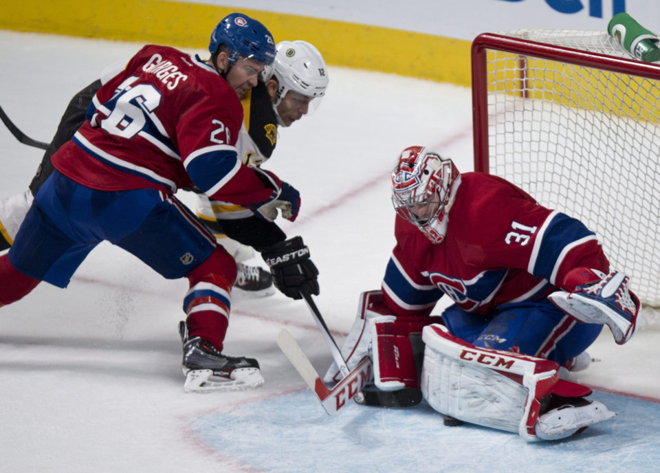 Photo - Montreal Canadiens goalie Carey Price stops a shot by Boston Bruins' Jarome Iginla as Canadiens defenseman Josh Gorges covers during third period NHL hockey action Thursday, Dec. 5, 2013, in Montreal. The Canadiens beat the Bruins 2-1. (AP Photo/The Canadian Press, Paul Chiasson)