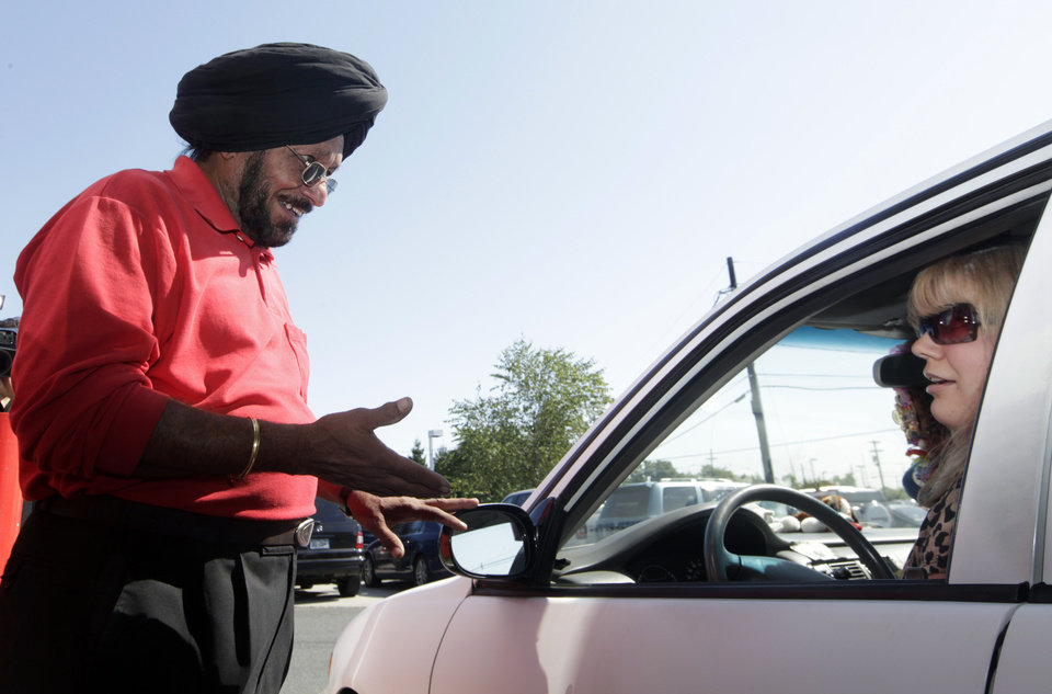 Photo -   Lukoil service station worker Harbhasan Singh explains Wednesday, Sept. 12, 2012, in South Plainfield, N.J., to regular customer Tiffany Price that as a protest to what they say are unfair pricing practices by Lukoil North America, the station has raised their gas price to more than $8 a gallon. Price still bought gas in support of the protest. More than 50 Lukoil gas stations in New Jersey and Pennsylvania were jacking up prices to more than $8 a gallon Wednesday to protest what they say are unfair pricing practices by Lukoil North America that they say leave them at a competitive disadvantage. (AP Photo/Mel Evans)