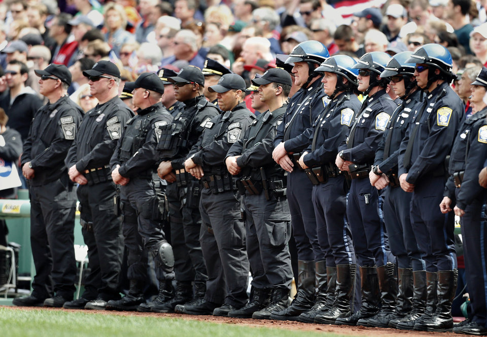 Boston police personnel stand on the field during ceremonies in honor of victims of and first responders to the Boston Marathon bombings, before a baseball game between the Boston Red Sox and the Kansas City Royals in Boston, Saturday, April 20, 2013. (AP Photo/Michael Dwyer) ORG XMIT: MAMD131