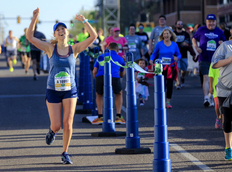 Photo - Jenna Jarvis reacts as she completes the half marathon during the Oklahoma City Marathon in Oklahoma City, Okla. on Sunday, April 29, 2018.  . Photo by Chris Landsberger, The Oklahoman