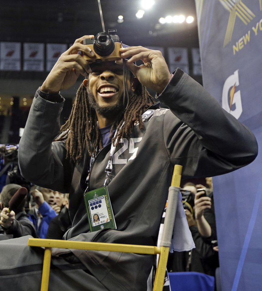 Photo - Seattle Seahawks' Richard Sherman takes a picture during media day for the NFL Super Bowl XLVIII football game Tuesday, Jan. 28, 2014, in Newark, N.J. (AP Photo/Jeff Roberson)