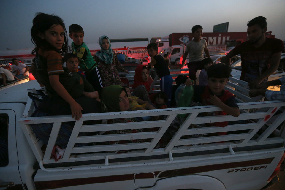 Photo - Fleeing Iraqi citizens from Mosul and other northern towns sit on a pick up as they wait in a long queue to cross to secure areas, in the Khazer area between the Iraqi city of Mosul and the Kurdish city of Irbil, northern Iraq, Wednesday June 25, 2014. Sunni insurgents who seized Iraq's second largest city attacked a nearby Christian village on Wednesday, bringing their fight closer to the largely Kurdish regions of northern Iraq which had remained so far largely untouched from the chaos sweeping the country. (AP Photo/Hussein Malla)