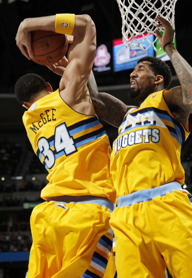 Photo - Denver Nuggets forwards JaVale McGee, left, and Wilson Chandler get tied up with each other on a rebound, against the Boston Celtics in the first quarter of an NBA basketball game in Denver on Tuesday, Feb. 19, 2013. (AP Photo/David Zalubowski)
