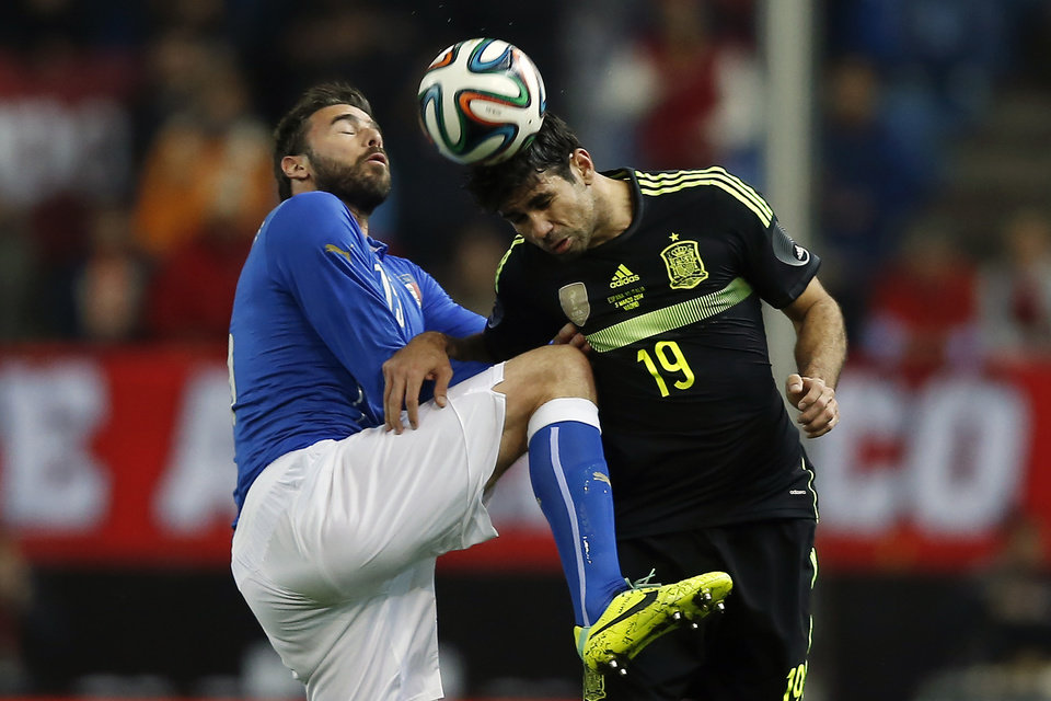 Photo - Spain's Diego Costa, right, in action with Italy's Andrea Barzagli, left, during a international friendly soccer match between Spain and Italy at the Vicente Calderon stadium in Madrid, Spain, Wednesday, March 5, 2014. (AP Photo/Andres Kudacki)