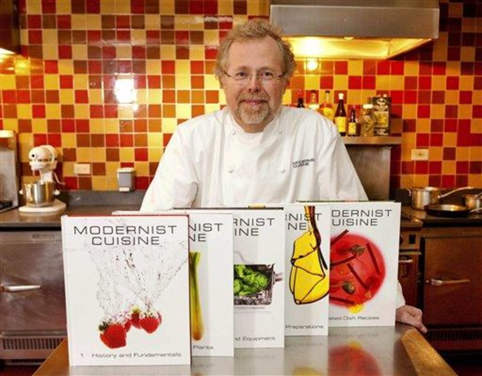 "FILE - This March 23, 2011 file photo shows Nathan Myhrvold, author of ""Modernist Cuisine: The Art and Science of Cooking,"" as he poses with books at the Institute for Culinary Education in New York. At times in 2012 it felt like the food world belonged to the geeks, and the rest of us just eat in it. Myhrvold's science chic approach to cooking continued to woo foodies, and even the more populist folks at Cook's Illustrated magazine got in on the act with a new cookbook, ""The Science of Good Cooking."" (AP Photo/Stephen Chernin, File)"