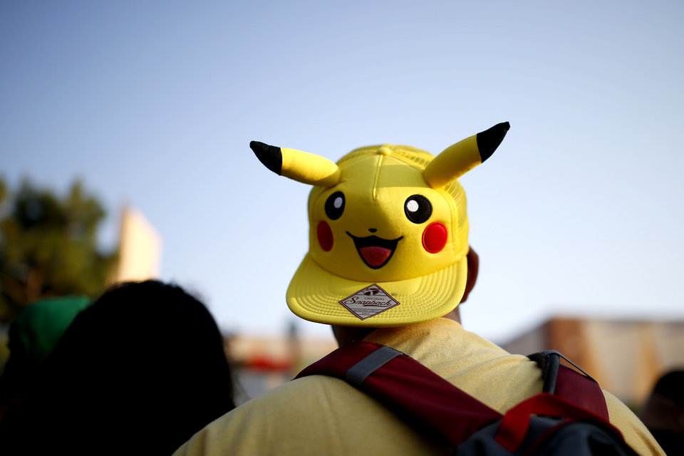 Photo - Anthony Acosta wears a Pikachu hat as he plays Pokemon Go during a meetup for players of the game in Oklahoma City at Bricktown on Friday, July 29, 2016. Photo by Bryan Terry, The Oklahoman