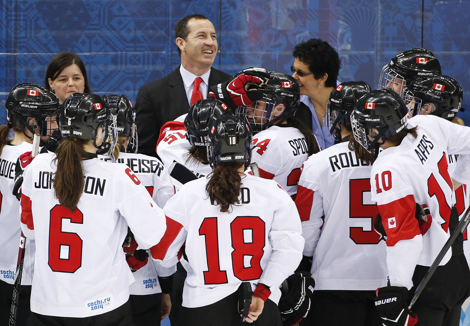 Photo - Canada head coach Kevin Dineen celebrates with players after Canada beat Switzerland 3-1 in a 2014 Winter Olympics women's semifinal ice hockey game at Shayba Arena, Monday, Feb. 17, 2014, in Sochi, Russia. (AP Photo/Julio Cortez)