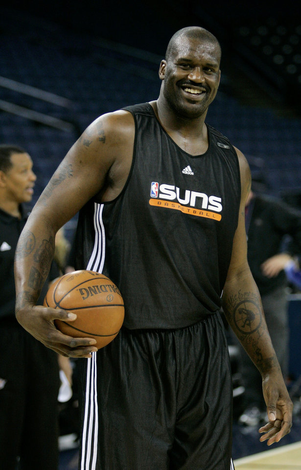 Photo - **FILE** Phoenix Suns center Shaquille O'Neal smiles during practice before an NBA basketball game against the Golden State Warriors in Oakland, Calif. in this Feb. 13, 2008 file photo. O'Neal is expected to make his Phoenix debut Wednesday, Feb 20, 2008, against the team he helped win three NBA titles, the Los Angeles Lakers, with his old coach Phil Jackson and former teammate Kobe Bryant. (AP Photo/Marcio Jose Sanchez, File) ORG XMIT: NY154