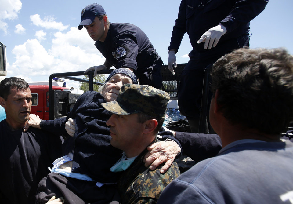 Photo - Police officers help an elderly women out of the police truck in Obrenovac, some 30 kilometers (18 miles) southwest of Belgrade, Serbia, Monday, May 19, 2014. Belgrade braced for a river surge Monday that threatened to inundate Serbia's main power plant and cause major power cuts in the crisis-stricken country as the Balkans struggle with the consequences of the worst flooding in southeastern Europe in more than a century. At least 35 people have died in Serbia and Bosnia in the five days of flooding caused by unprecedented torrential rain, laying waste to entire towns and villages and sending tens of thousands of people out of their homes, authorities said. (AP Photo/Darko Vojinovic)