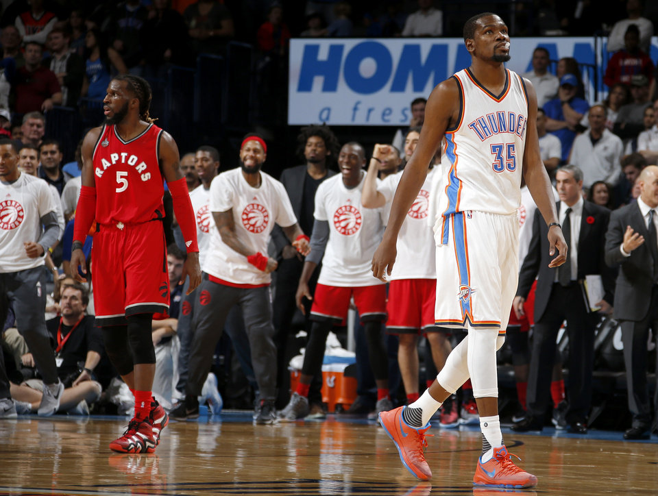 Photo - Oklahoma City's Kevin Durant (35) walks away as Toronto's DeMarre Carroll (5) and other Toronto players celebrate a foul on the Thunder in the final seconds of an NBA basketball game between the Oklahoma City Thunder and the Toronto Raptors at Chesapeake Energy Arena on Wednesday, Nov. 4, 2015. The Thunder lost 103-98. Photo by Bryan Terry, The Oklahoman