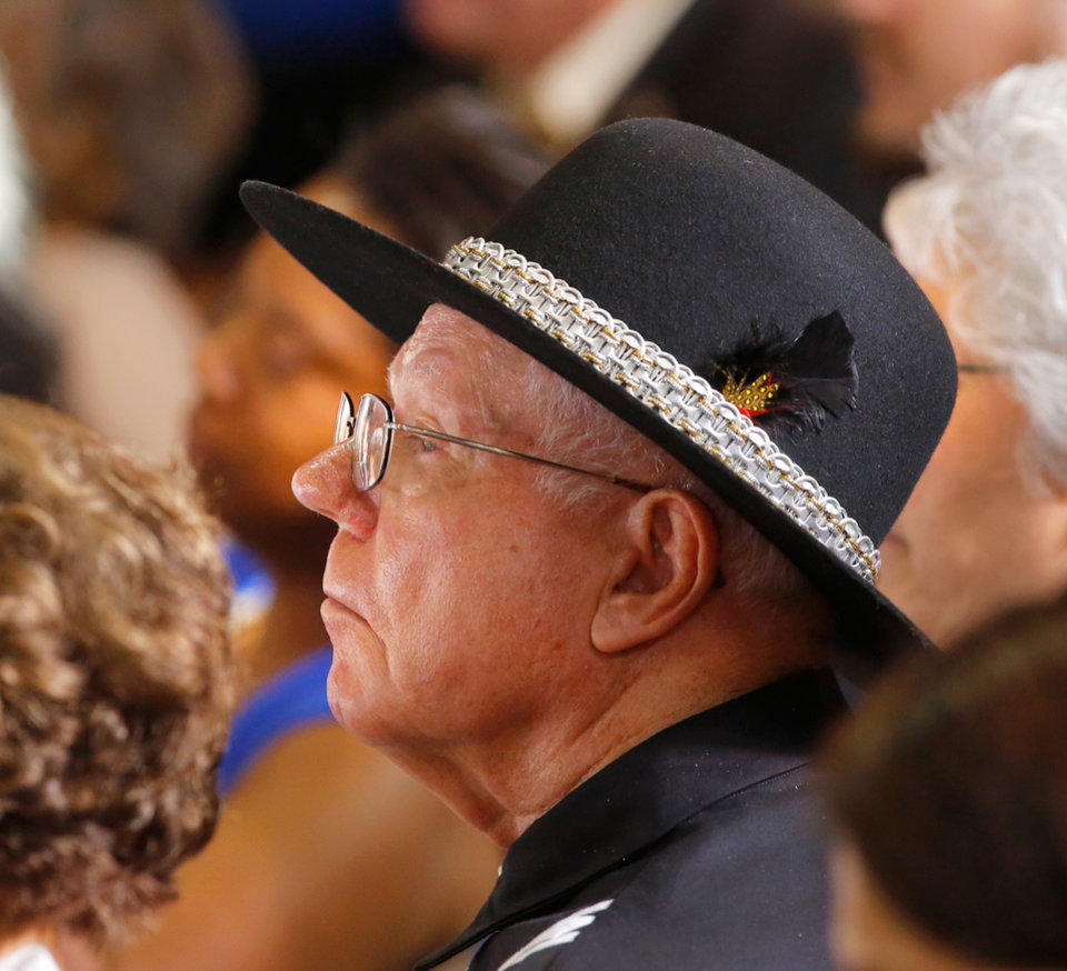 Photo - A man in traditional Choctaw Nation clothing listens to President Barack Obama speaking to about 950 people in Durant's new high school on Wednesday, July 15, 2015.  He used his visit in Durant to announce his administration's newest initiative, ConnectHome. It's described as a cooperative effort with communities, the private sector and federal government  to expand high speed broadband to more families across the country. The pilot program is launching in 27 cities and one tribal nation, the Choctaw Nation in southeast Oklahoma. Photo by Jim Beckel, The Oklahoman.