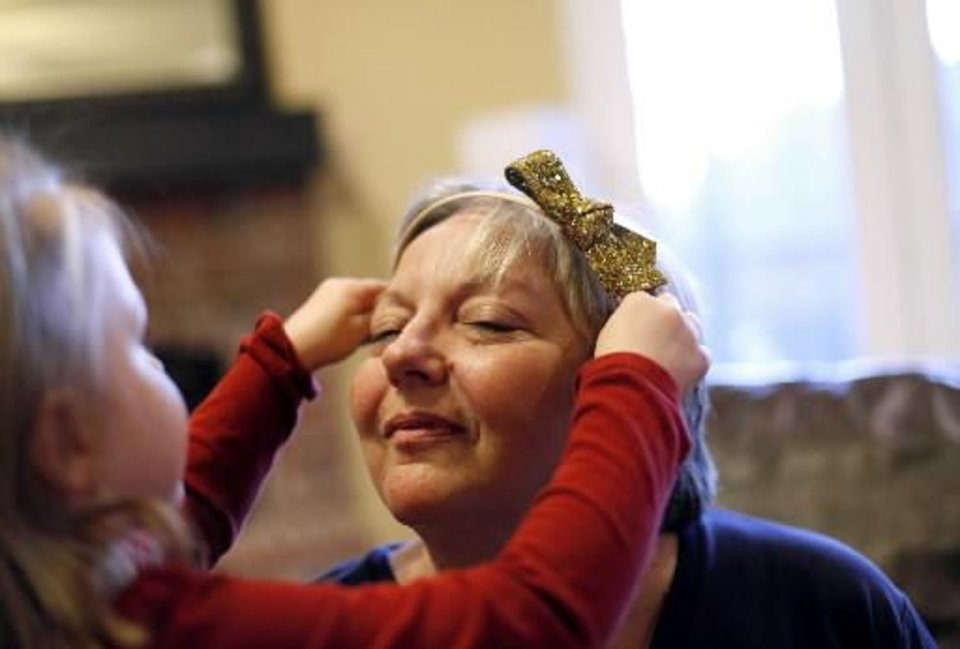 Photo - Marsha Patton gets her hair 'styled' during playtime with her granddaughter Taylor Hurst, 4, at her daughter's home in Broken Arrow, Okla., Thursday, Feb. 23, 2012. A recovering heroin addict, Marsha says she tries to spend as much time as she can with her grandkids. JOHN CLANTON/Tulsa World