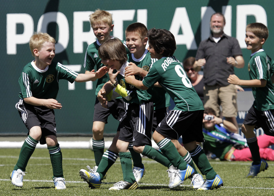 Photo - Atticus Lane-Dupre, 8, third from left, is congratulated by his teammates on the Green Machine soccer team after scoring the winning goal against the MLS Portland Timbers soccer team in Portland, Ore., Wednesday, May 1, 2013.  The Timbers and Make-A-Wish Oregon treated Atticus' team to a game at Jeld-Wen Field with more than 3,000 fans coming out to lend their support. Atticus missed the Green Machine's final match last fall because of cancer treatment.  (AP Photo/Don Ryan)