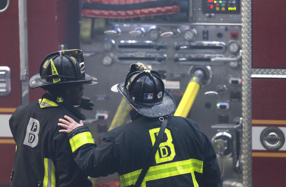 Photo - ADDS LAST SENTENCE - A firefighter places his hand on the shoulder of another at the scene of a multi-alarm fire at a four-story brownstone in the Back Bay neighborhood near the Charles River, Wednesday, March 26, 2014 in Boston. A Boston city councilor said two firefighters have died in a fire that ripped through a brownstone. (AP Photo/Steven Senne)