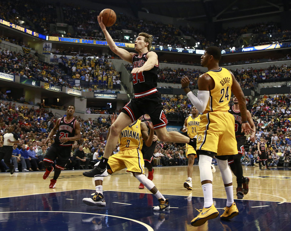 Photo - Chicago Bulls forward Mike Dunleavy (34) shoots after getting past Indiana Pacers forward Paul George (24) in the first half of an NBA basketball game in Indianapolis, Friday, March 21, 2014. (AP Photo/R Brent Smith)