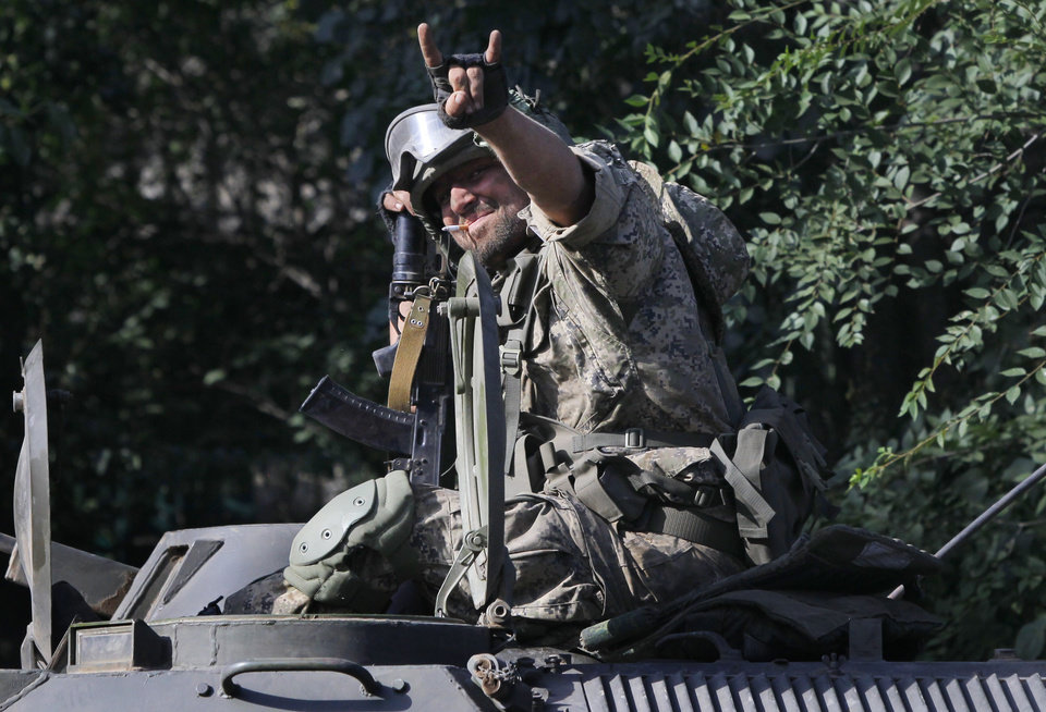 Photo - Pro-Russian rebel rides on an APC in the town of Krasnodon, eastern Ukraine, Sunday, Aug. 17, 2014. A column of several dozen heavy vehicles, including tanks and at least one rocket launcher, rolled through rebel-held territory on Sunday.(AP Photo/Sergei Grits)