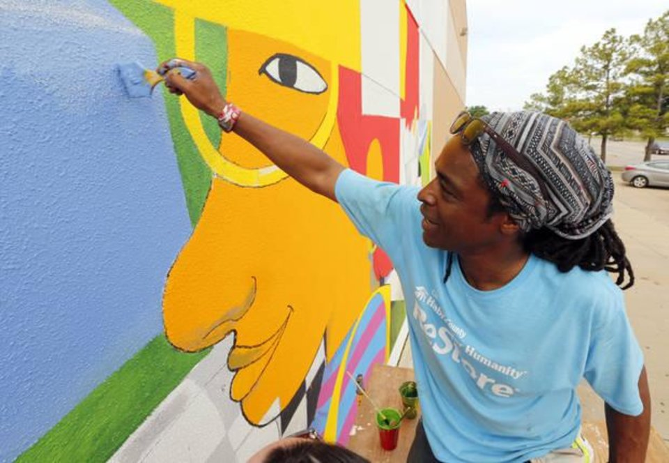 Photo - Norman artist Skip Hill creates a mural on the Main Street side of the future Habitat for Humanity Store on Friday, July 3, 2015 in Norman, Okla. Hill will be among the 14 Oklahoma artists participating in a special art show for World AIDS Day. Photo by Steve Sisney, The Oklahoman Archives