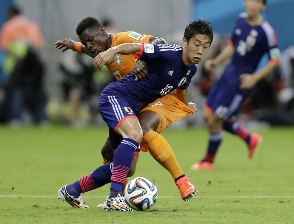 Photo - Japan's Shinji Kagawa, front, battles for the ball with Ivory Coast's Serge Aurier during the group C World Cup soccer match between Ivory Coast and Japan at the Arena Pernambuco in Recife, Brazil, Saturday, June 14, 2014. (AP Photo/Ricardo Mazalan)