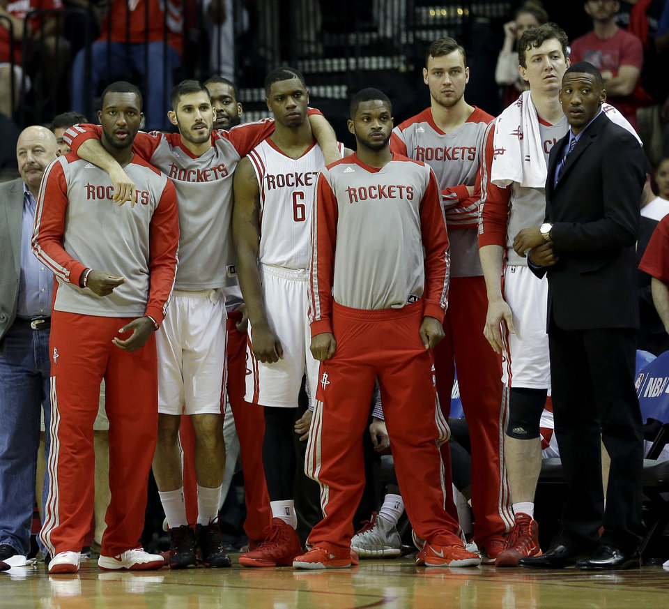 Photo - Members of the Houston Rockets watch from the bench during overtime in Game 1 of an opening-round NBA basketball playoff series against the Portland Trail Blazers Sunday, April 20, 2014, in Houston. The Trail Blazers won 122-120 in overtime. (AP Photo/David J. Phillip)