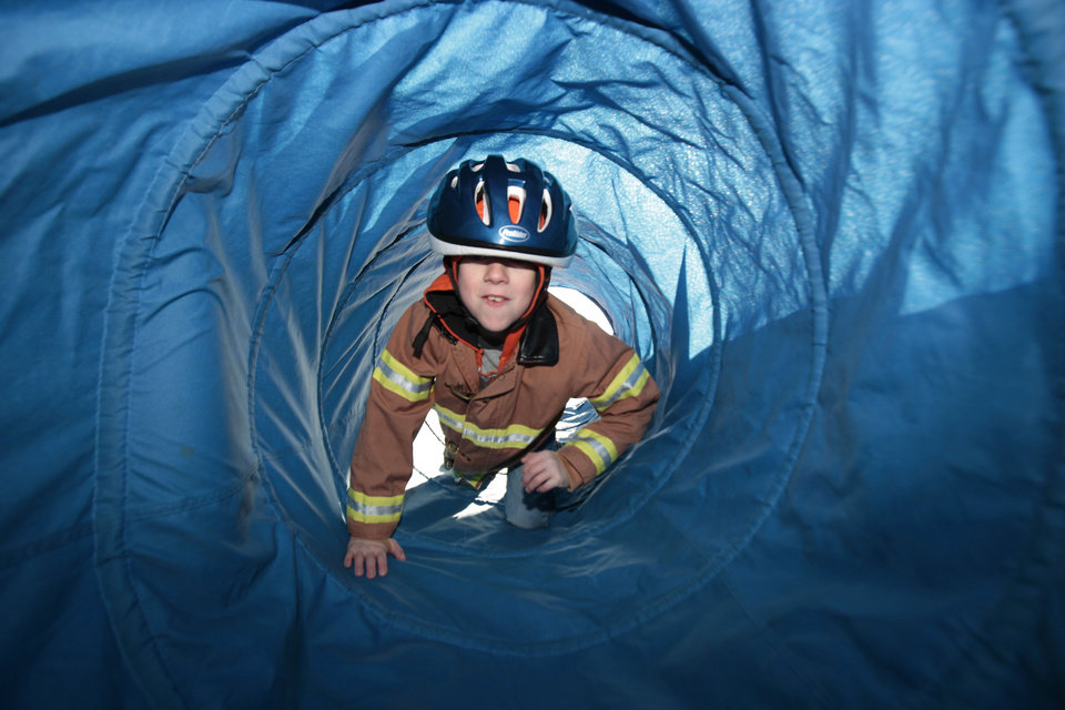Zachery Duck, 7, climbs through a tunnel representing smoke during Edmond Fire Department's Children's Safety Challenge over spring break. PHOTO BY DAVID MCDANIEL, THE OKLAHOMAN