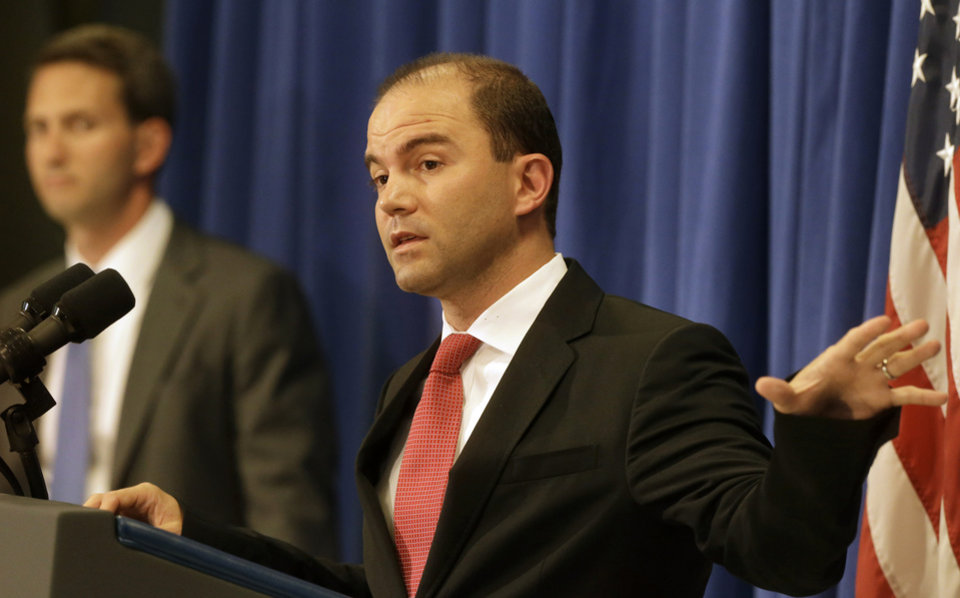 Photo - Deputy National Security Adviser for Strategic Communications and Speechwriting Ben Rhodes, right, accompanied by Deputy Press Secretary Eric Schultz, left, faces reporters during a press briefing, in Edgartown, Mass., on the island of Martha's Vineyard, Friday, Aug. 22, 2014. Rhodes spoke on issues concerning the situation in Iraq and Ukraine. (AP Photo/Steven Senne)