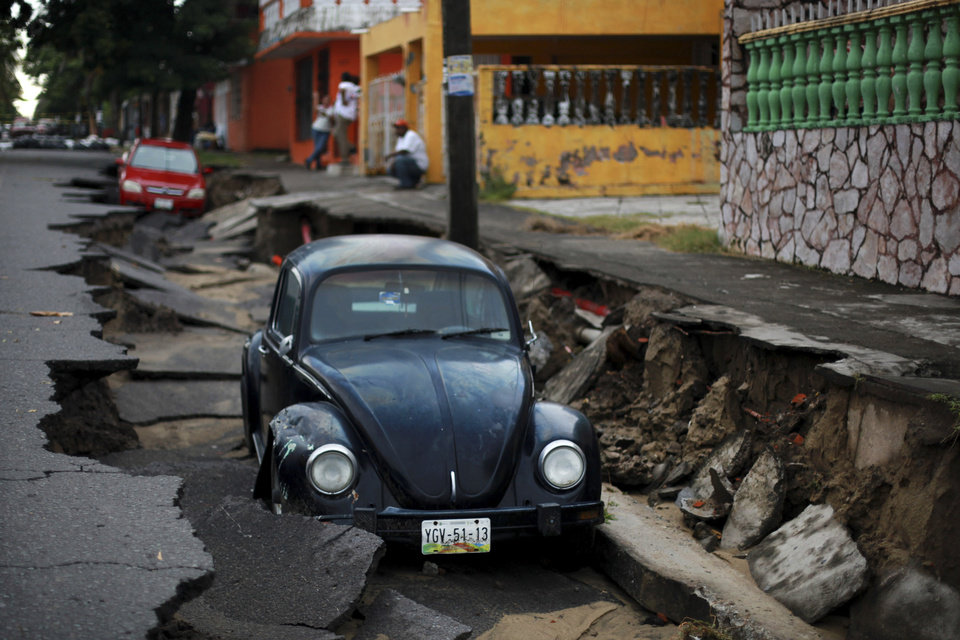 Photo - A couple of cars lie in a portion of a collapsed street due to heavy rains in the Gulf port city of Veracruz, Mexico, Tuesday Sept. 2, 2014. The Gulf states of Mexico are bracing for more bad weather as Tropical Storm Dolly will cross the coast lat this evening or overnight and continue moving inland over northeastern Mexico on Wednesday. (AP Photo/Felix Marquez)