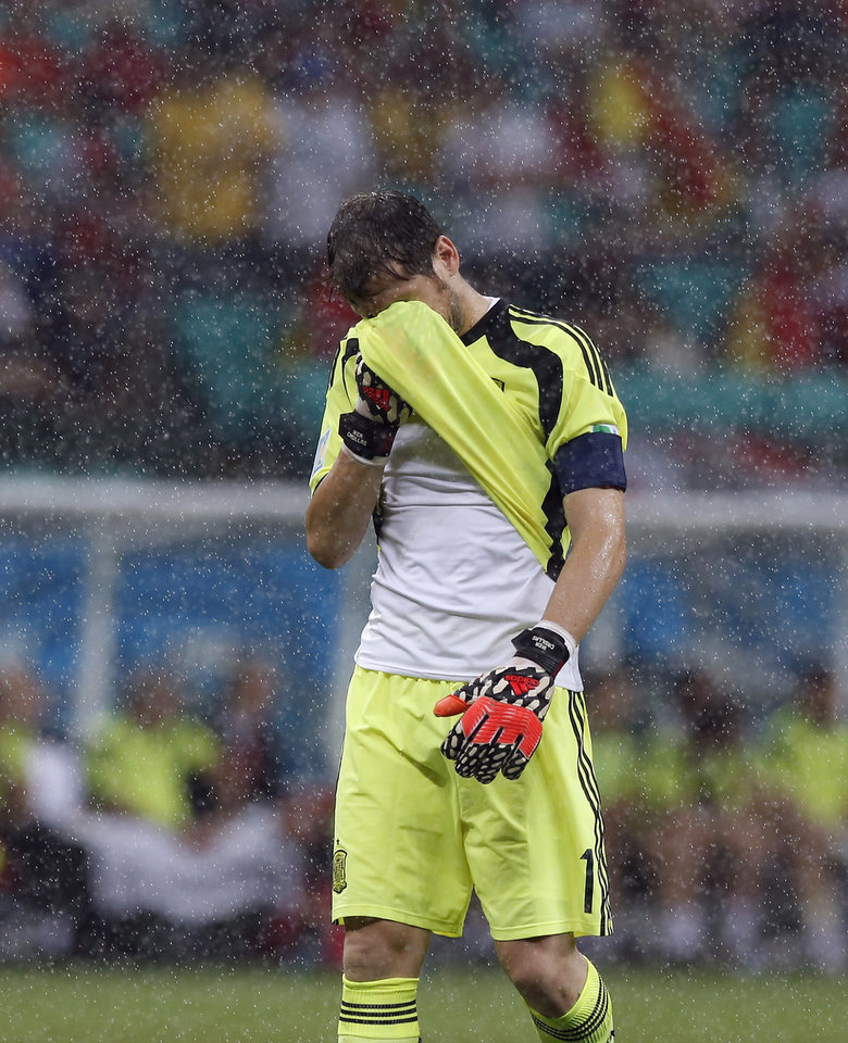 Photo - Spain's goalkeeper Iker Casillas wipes his face after Netherlands scored their fourth goal during the second half of the group B World Cup soccer match between Spain and the Netherlands at the Arena Ponte Nova in Salvador, Brazil, Friday, June 13, 2014. (AP Photo/Wong Maye-E)