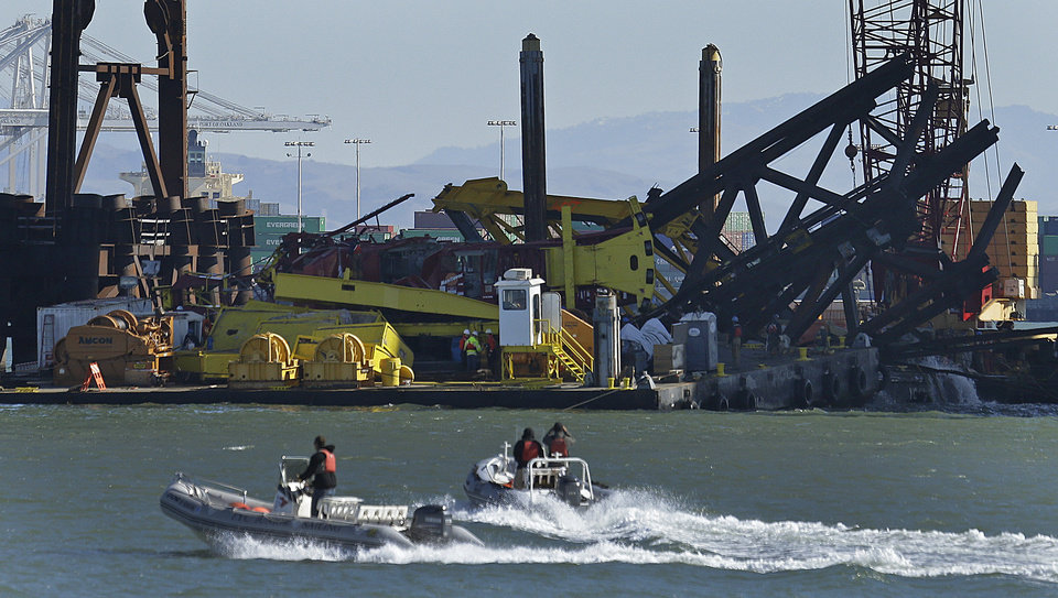 Photo - Investigators approach the scene where a crane overturned onto a barge and into San Francisco Bay, seen from Clipper Cove on Treasure Island Thursday, Feb. 21, 2013, in San Francisco. A crane tipped over while working on the new eastern span of the San Francisco-Oakland Bay Bridge on Thursday afternoon, but there were no injuries and nothing leaked into the bay, authorities said. (AP Photo/Ben Margot)