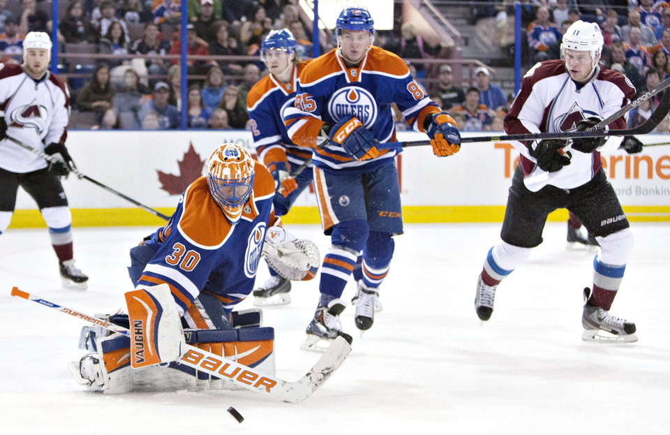 Photo - Colorado Avalanche's Jamie McGinn (11) and Edmonton Oilers' Jeff Petry (2) and Martin Marincin (85) chase the rebound as goalie Ben Scrivens (30) makes the save during first period NHL hockey action in Edmonton, Alberta, on Tuesday April 8, 2014. (AP Photo/The Canadian Press, Jason Franson)