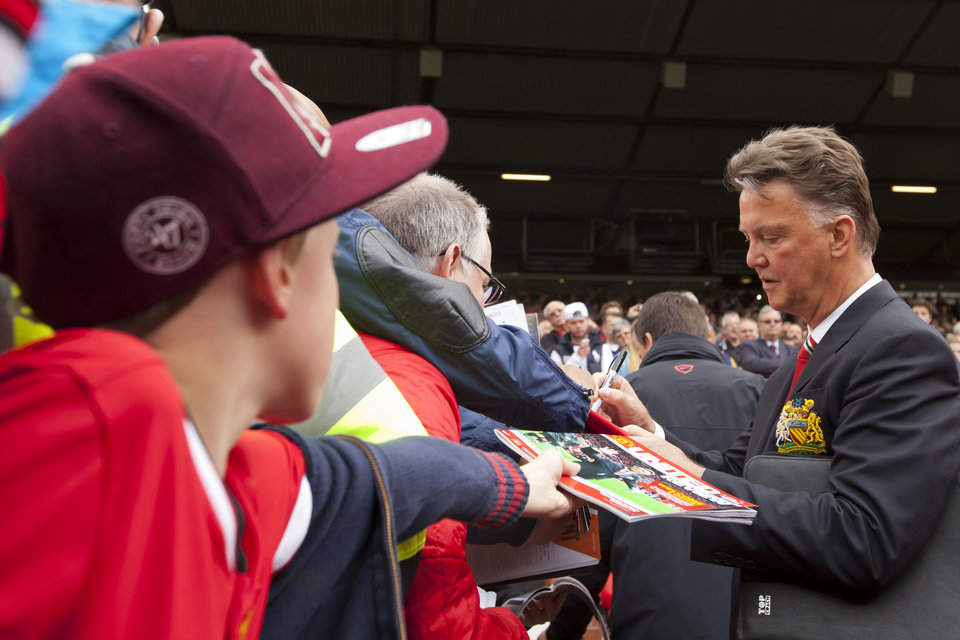 Photo - Manchester United's new manager Louis van Gaal signs autographs before his team's English Premier League soccer match against Swansea City at Old Trafford Stadium, Manchester, England, Saturday Aug. 16, 2014. (AP Photo/Jon Super)