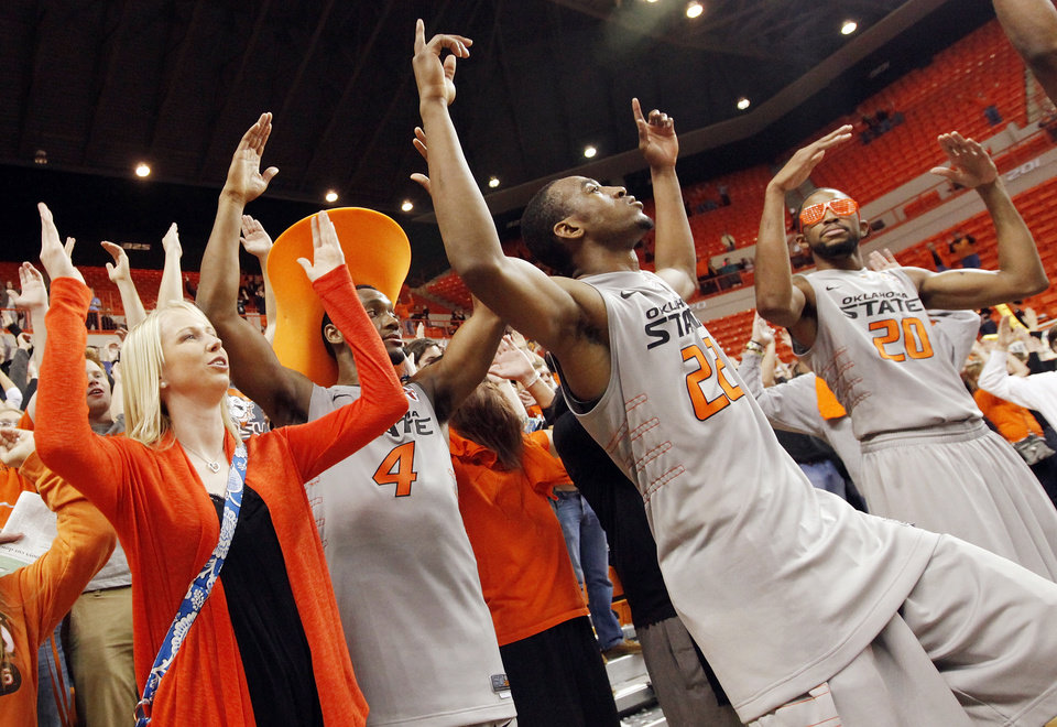 Photo - OSU's Brian Williams (4), Markel Brown (22) and Michael Cobbins (20) sing the alma mater with fans after the Bedlam men's college basketball game between the Oklahoma State University Cowboys and the University of Oklahoma Sooners at Gallagher-Iba Arena in Stillwater, Okla., Monday, Jan. 9, 2012. OSU beat OU, 72-65. Photo by Nate Billings, The Oklahoman