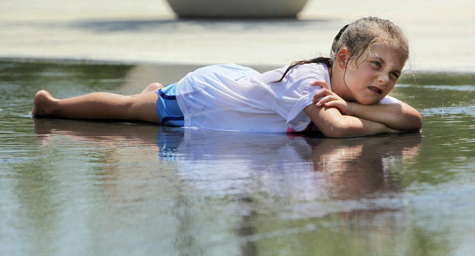 Photo - HEAT / SUMMER / HOT WEATHER / CHILD / CHILDREN / KIDS: Kendall Tighe, 7, keep cool by resting in a pool of water at a fountain in the Myriad Gardens during high temperatures in Oklahoma City, Monday, June 25, 2012. Photo by Nate Billings, The Oklahoman