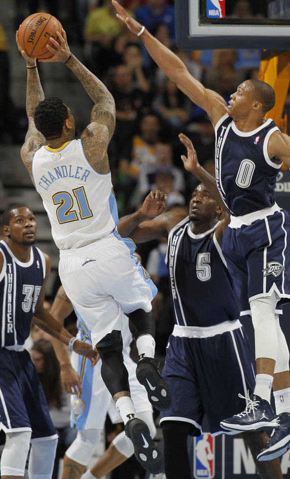 Denver Nuggets forward Wilson Chandler (21) goes up for a shot as Oklahoma City Thunder guard Russell Westbrook, front right, forward Kevin Durant, back left, and center Kendrick Perkins (5) cover in the first quarter of an NBA basketball game in Denver on Friday, March 1, 2013. (AP Photo/David Zalubowski) ORG XMIT: CODZ103