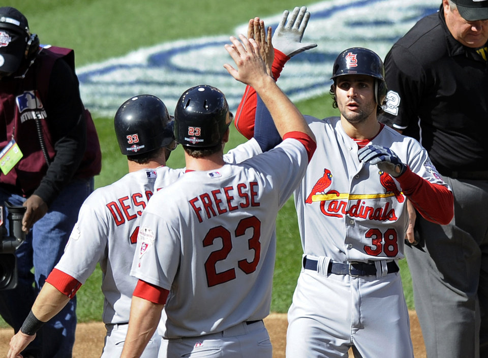 Photo -   St. Louis Cardinals' Pete Kozma, right, high-fives teammates David Freese and Daniel Descalso after batting them with on a three-run home run in the second inning of Game 3 of the National League division baseball series against the Washington Nationals on Wednesday, Oct. 10, 2012, in Washington. (AP Photo/Nick Wass)