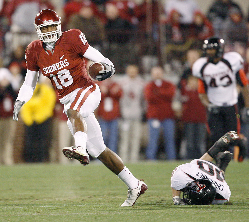 Photo - OU's Jermaine Gresham runs past Daniel Charbonnet of Texas Tech during the college football game between the University of Oklahoma Sooners and Texas Tech University at Gaylord Family -- Oklahoma Memorial Stadium in Norman, Okla., Saturday, Nov. 22, 2008. BY BRYAN TERRY, THE OKLAHOMAN ORG XMIT: KOD