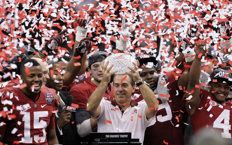 Photo - FILE - In this Jan. 9, 2012 file photo, Alabama head football coach Nick Saban celebrates with his team after the BCS National Championship college football game against LSU  in New Orleans. Saban's new contract _ expected to be in the $7 million range _ is set to be formally considered by the board of trustees. The trustees will also vote on deals for 10 of his assistants, including new offensive coordinator Lane Kiffin. (AP Photo/Gerald Herbert, File)