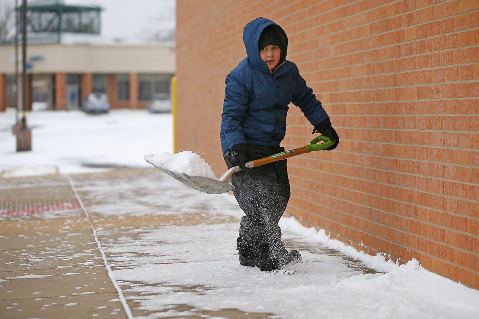 Photo - Anthony Ignacio, 11, helps his dad clear snow outside a pharmacy in northwest Oklahoma City during a winter storm, Sunday, Feb. 14, 2021. [Bryan Terry/The Oklahoman]