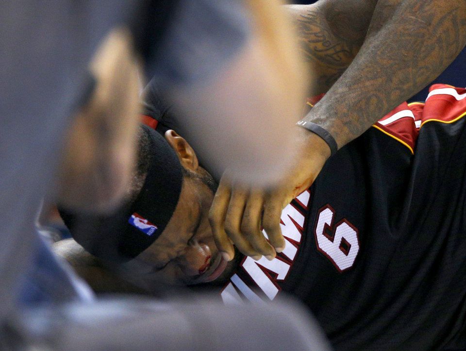 Photo - Bloods comes from Miami's LeBron James (6) nose after a play during an NBA basketball game between the Oklahoma City Thunder and the Miami Heat at Chesapeake Energy Arena in Oklahoma City, Thursday, Feb. 20, 2014. Oklahoma CIty lost 103-81. Photo by Bryan Terry, The Oklahoman