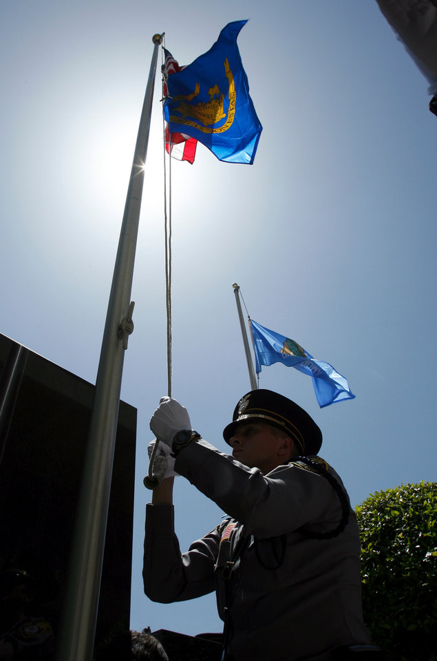 Photo - The honor guard raises the flag during a ceremony remembering fallen officers at a memorial in front of Oklahoma City Police Headquarters in Oklahoma City, Oklahoma on Friday, May 9, 2008.   BY STEVE SISNEY, THE OKLAHOMAN    ORG XMIT: KOD