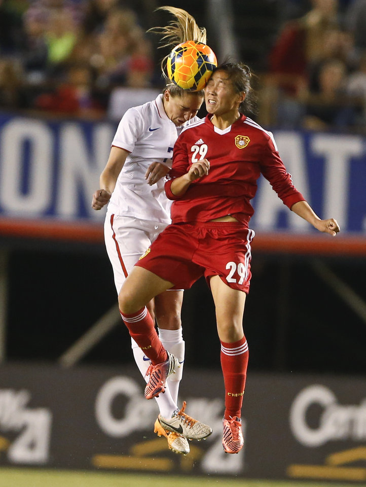 Photo - China forward Yang Li and U.S. midfielder Morgan Brian vie for a head ball during the first half of an international friendly soccer match Thursday, April 10, 2014, in San Diego. (AP Photo/Lenny Ignelzi)