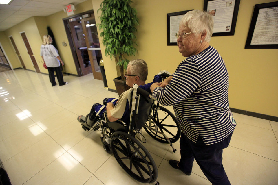 B.J. Matthews walks with her husband, Bob Matthews, at an Oklahoma City rehabilitation center Tuesday. Bob Matthews contracted West Nile virus this past summer and is working to recover. Recovering from West Nile virus can be a slow and painful process. Photo by Sarah Phipps, The Oklahoman <strong>SARAH PHIPPS</strong>