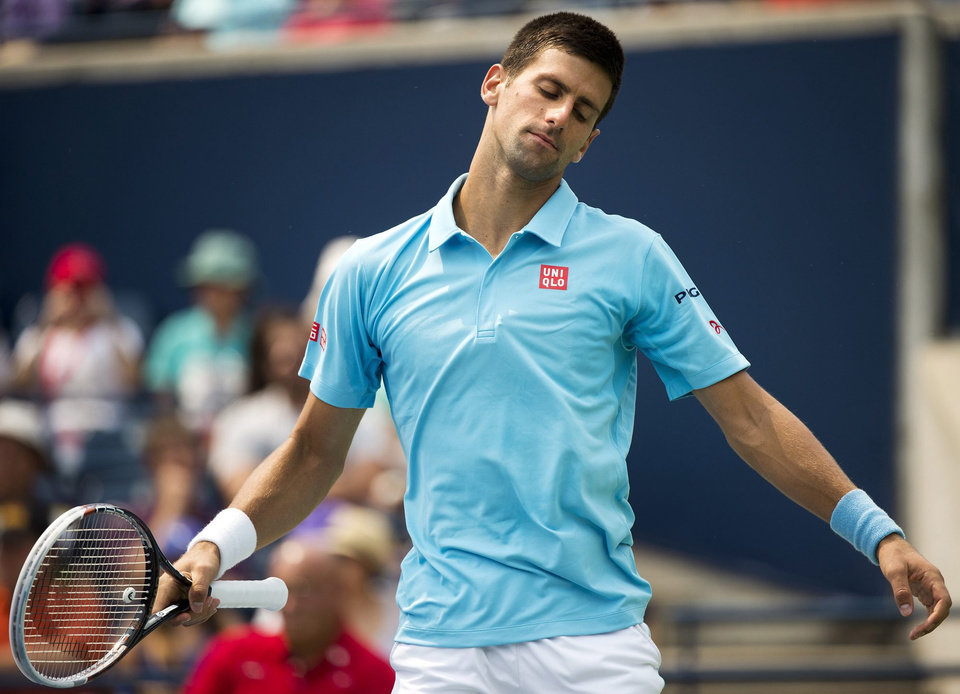 Photo - Novak Djokovic, of Serbia, reacts while playing against Jo-Wilfried Tsonga, of France, in a men's third round match at the Rogers Cup tennis tournament action in Toronto Thursday, Aug. 7, 2014. (AP Photo/The Canadian Press, Nathan Denette)