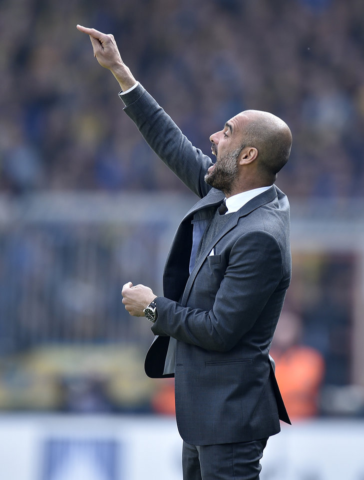 Photo - Bayern head coach Pep Guardiola of Spain shouts to his team during the German Bundesliga soccer match between Eintracht Braunschweig and Bayern Munich in Braunschweig, Germany, Saturday, April 19, 2014. (AP Photo/Martin Meissner)