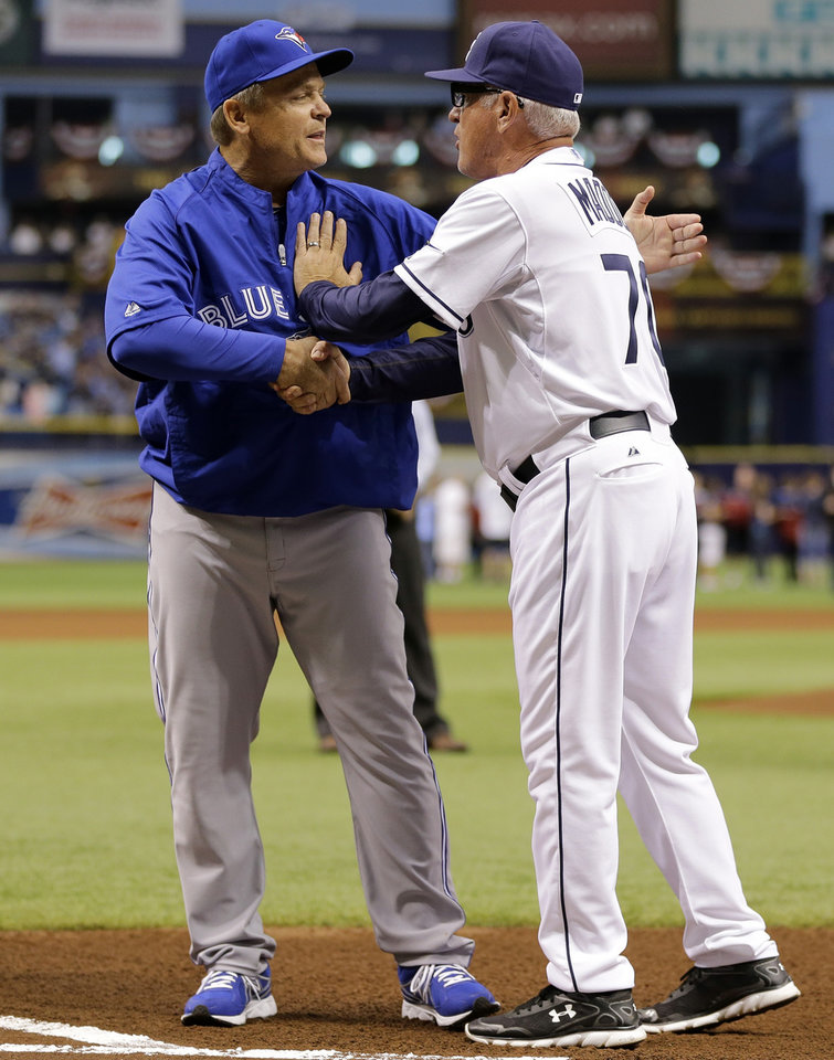 Photo - Toronto Blue Jays manager John Gibbons, left, shakes hands with Tampa Bay Rays manager Joe Maddon before a baseball game Monday, March 31, 2014, in St. Petersburg, Fla. (AP Photo/Chris O'Meara)