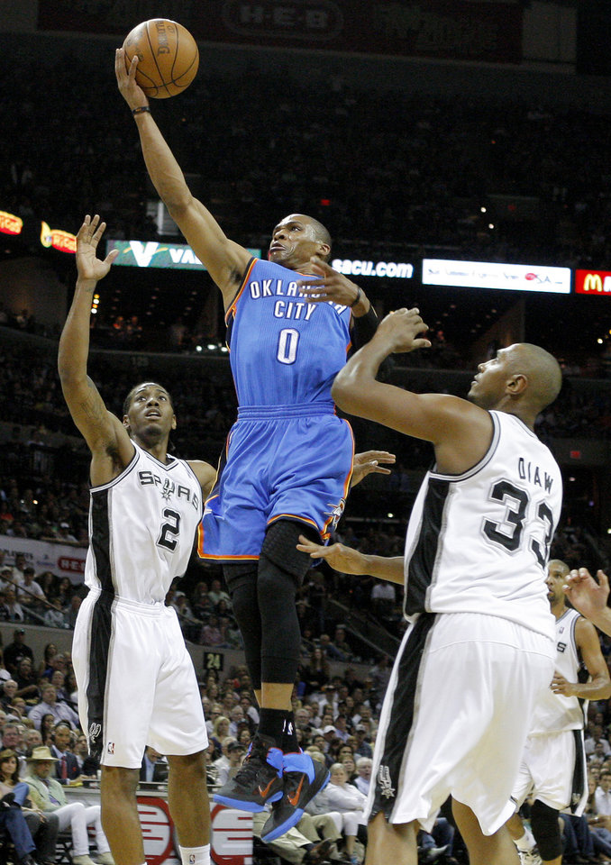 Photo - Oklahoma City's Russell Westbrook (0) goes to the basket between San Antonio's Kawhi Leonard (2) and Boris Diaw (33) during Game 1 of the Western Conference Finals between the Oklahoma City Thunder and the San Antonio Spurs in the NBA playoffs at the AT&T Center in San Antonio, Texas, Sunday, May 27, 2012. Photo by Bryan Terry, The Oklahoman