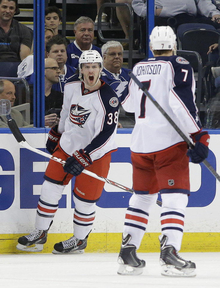 Photo - FILE - In this April 11, 2014 file photo, Columbus Blue Jackets center Boone Jenner (38) celebrates with defenseman Jack Johnson (7) after scoring against the Tampa Bay Lightning during an NHL hockey game  in Tampa, Fla. Few people outside of their dressing room think the Blue Jackets have even a remote chance of beating the Pittsburgh Penguins in the first round of the Stanley Cup playoffs. After years of being an NHL doormat, they're used to being overlooked. (AP Photo/Chris O'Meara, File)